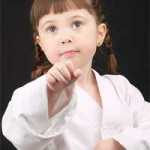 young girl in karate uniform practising a punch