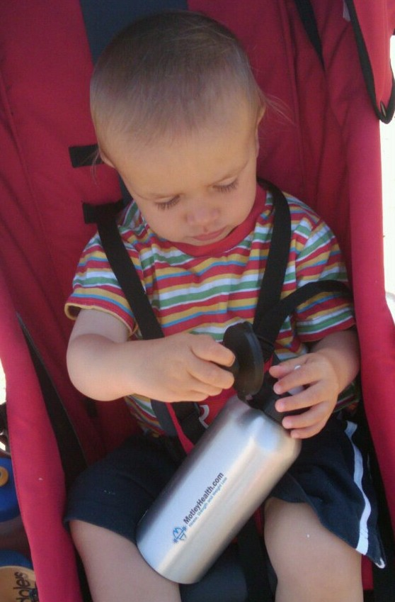 young child holding a water bottle