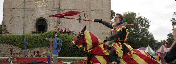 A knight charging on his horse, carry a red flag