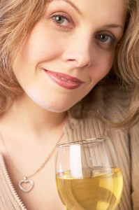 Smiling woman holding glass of white wine