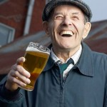 Laughing elderly man drinking glass of beer