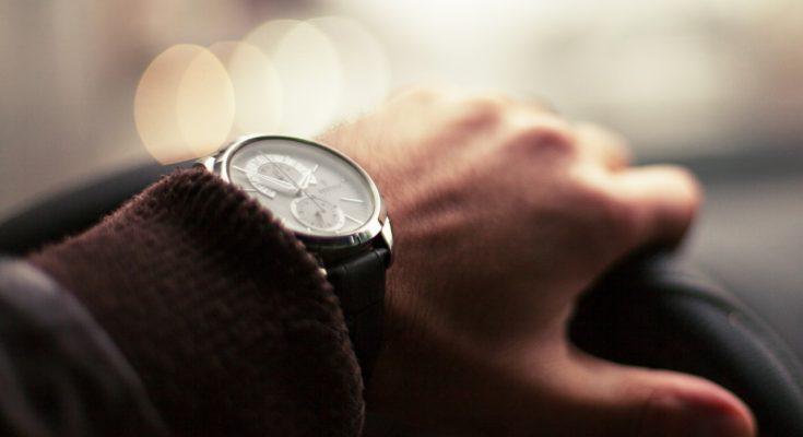 stylish watch on wrist of man driving a car