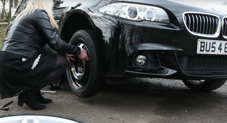 woman changing car tyre with the oad hero space saver kit